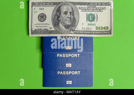 Three blue biometric passports with one hundred dollar bill are located vertically - Stock Photo