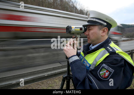 26 March 2018, Germany, Wuppertal: A police officer measures the speed of passing cars with a laser pistol. North Rhine-Westphalia's Interior Minister Herbert Reul of the Christian Democratic Union (CDU) promotes greater safety measures at the beginning of motorcycling season. Photo: Oliver Berg/dpa - Stock Photo