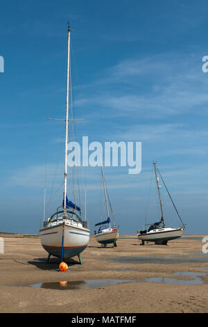 Sailing boats stranded on beach at Red Wharf Bay at low tide - Stock Photo