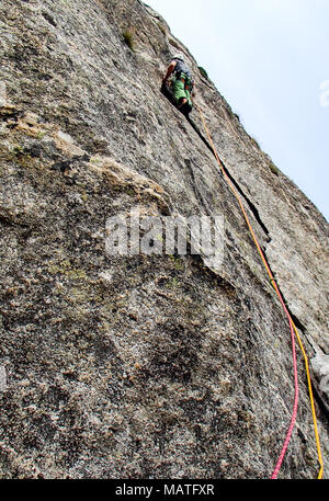 rock climber dressed in bright colors on a steep granite climbing route in the Alps - Stock Photo