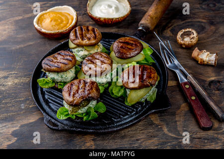 Grilled portobello bun mushroom burgers on cast iron grill pan ob wooden background, top view. - Stock Photo