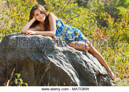 Young woman brunette, 20 years old, lying and leaning on a rock and with a smile looking at the camera. Shines the bright sun. - Stock Photo