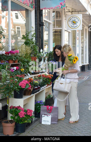 Two women browsing a florist display, south street, Eastbourne, East Sussex, England, UK - Stock Photo