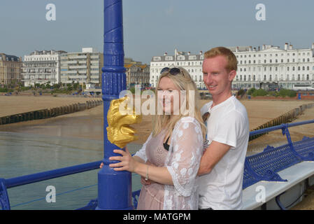 A young couple on Eastbourne pleasure pier, East Sussex, England, UK - Stock Photo