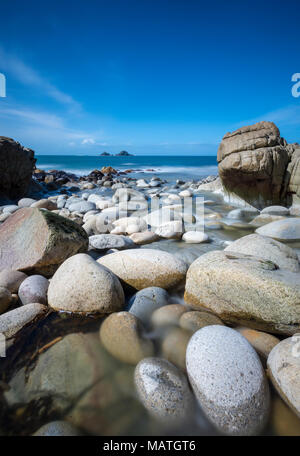 A beautiful and atmospheric Cornish coastal scene at porth nanven close to the cot valley and lands end in cornwall. Large round boulders on the beach - Stock Photo