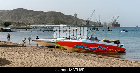 Aqaba, Jordan, March 3, 2018: Main beach west of the centre and promenade of Aqaba, private speedboats and small excursion boats have moored on the be - Stock Photo