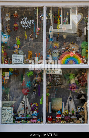 An eclectic mix of toys and various interesting items in the window of a small coastal cottage on the Cornish coast. Old curiosity shop window display - Stock Photo