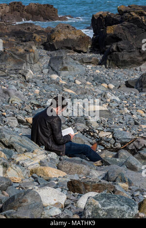 a man sitting on the beach reading a book relaxing. Enjoying reading while sat on the foreshore on a rocky beach in cornwall near the sea and waves. - Stock Photo