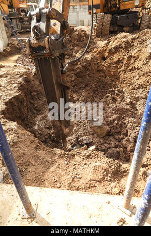 Excavator with a jackhammer breaks rocks in the ground. Deepening of foundation pit for foundation installation - Stock Photo