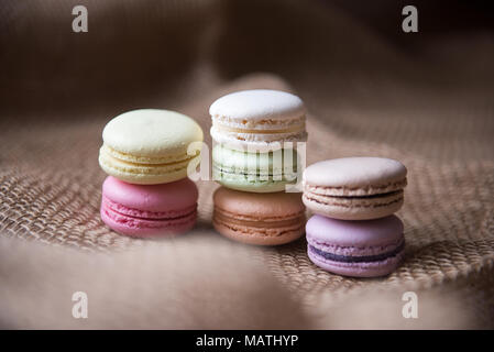 Sweet French macaroons cake (or macarons) with vintage pastel colored tone on pink background. - Stock Photo