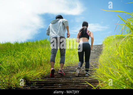 Athletic couple running upstairs in the forest trail - Stock Photo
