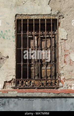 old window with wooden shutters and rusty fence on a chipped wall in a building in Madrid. Spain - Stock Photo