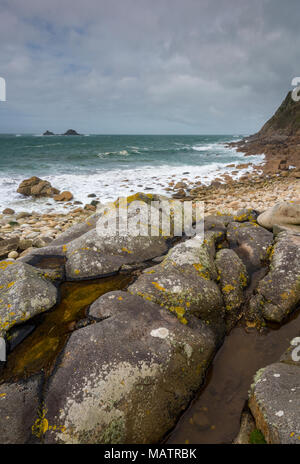 The beautiful and scenic atmospheric coastline at porth nanven on the Cornish coast in the cot valley near st just in cornwall. Large rocks on beach. - Stock Photo