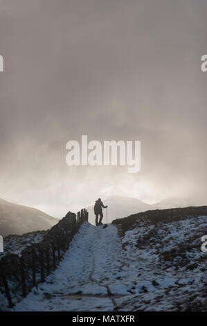 A man walking in the snow with the help of a walking stick along a path in the winter under a dark sky - Stock Photo
