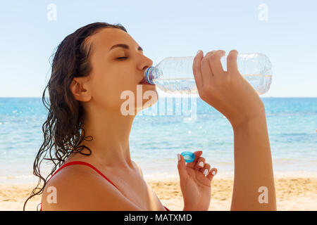 Young woman in a red swimsuit, drinking sparkling water from a transparent bottle on the beach. - Stock Photo