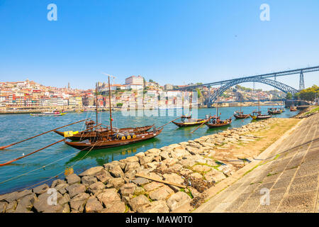 Porto, Portugal - August 13, 2017: Picturesque old Oporto waterfront with Ribeira skyline. A traditional rabelo boats on Douro River with Dom Luis I Bridge from Vila Nova de Gaia, Porto. Sunny day. - Stock Photo