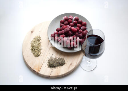 Glass of red wine, frozen cherries on grey concrete plate, rosemary and thyme spices on wooden cutting board isolated on white background - Stock Photo