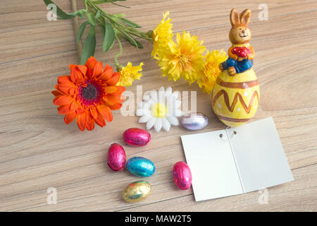 Easter greeting card with colored eggs candies, ceramic rabbit and flowers, on wood table with Copy space background. - Stock Photo