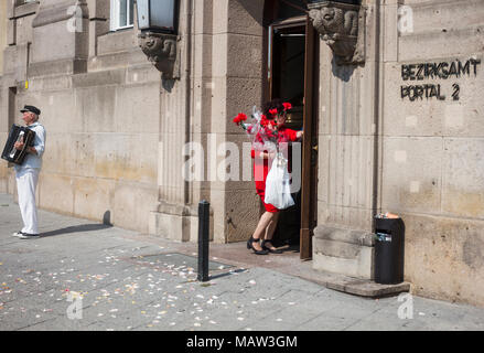 A woman in red carrying red flowers in Berlin, Germany. - Stock Photo