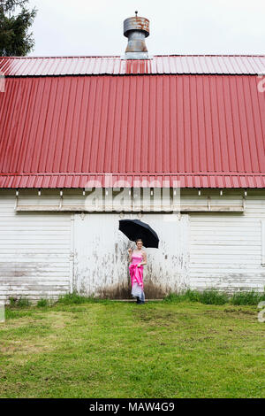 A girl in a pink prom dress, standing in the rain. - Stock Photo