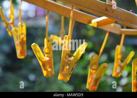 yellow cloth pin hanging in garden - Stock Photo
