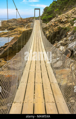 Perspective view of Suspension Bridge over Storms River Mouth in Tsitsikamma National Park, Eastern Cape, near Plettenberg Bay in South Africa. Popular tourist destination along Garden Route. - Stock Photo