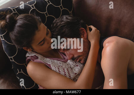 Couple sleeping together in living room - Stock Photo