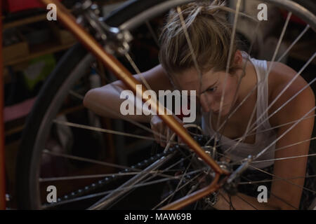 Female mechanic fixing bicycle in workshop - Stock Photo