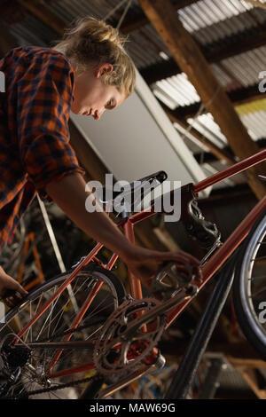 Female mechanic examining a bicycle - Stock Photo
