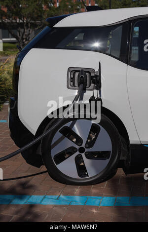 Electric car being charged at charging station - Stock Photo