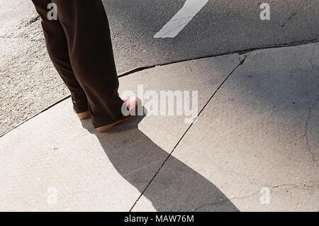 A person standing on a corner. - Stock Photo