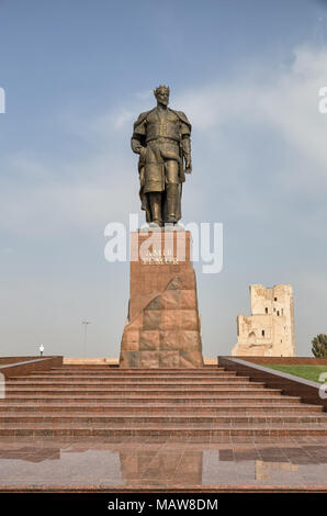 SHAKHRISABZ, UZBEKISTAN - OCTOBER 16, 20146: Monument to Amir Timur against the background of the blue sky and the ruins of Ak-Saray Palace - Stock Photo