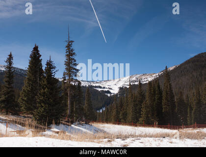 Snowy Meadow Landscape with Snow-Capped Mountains in the Background, Contrail in the Bright Blue Sky, at Rocky Mountain National Park in Colorado - Stock Photo