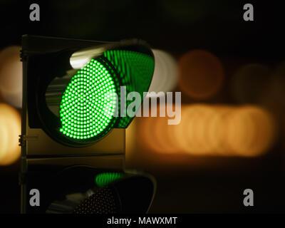 Green traffic light in the dark night city street. 3d rendering illustration - Stock Photo