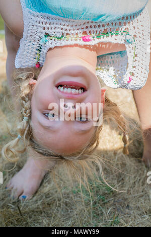 A young girl 4-6 years old, being held upside down. - Stock Photo