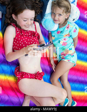 Two young girls using a digital tablet. One is 7-9 years old, the other is 4-6 years old. - Stock Photo