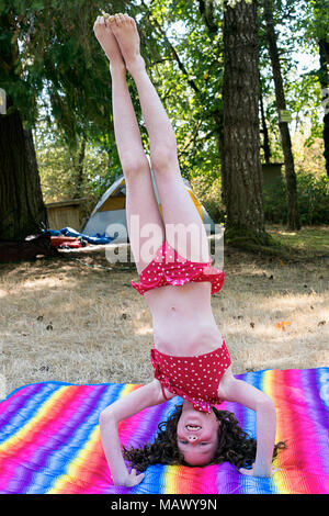 A young girl doing a headstand on a blanket 7-10 years old. - Stock Photo
