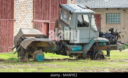 Side view of old disassembled tractor with engine with detached cylinder head and visible pistons - Stock Photo