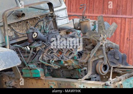 Old outworn disassembled Russian tractor engine with detached cylinder head and visible pistons - Stock Photo
