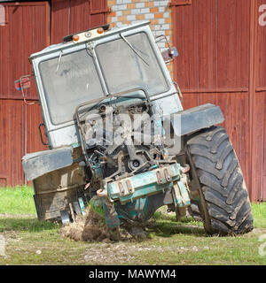 Old dismantled tractor with removed engine compartment hood and visible fan front view - Stock Photo