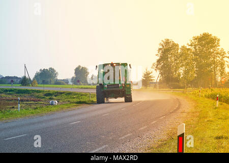 Tractor rides on the asphalt road in sunlight - Stock Photo