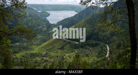 A thin road cut in to the volcanic hills around Lake Toba winds down to the lake viewed from west side through the surrounding trees. Sumatra, Indones - Stock Photo