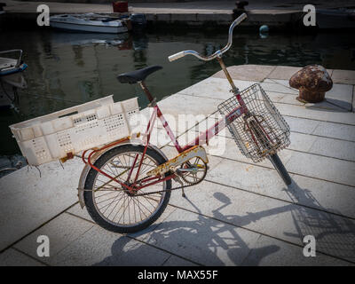 An old rusty bicycle of a fisherman standing in the harbor of Cres Croatia - Stock Photo