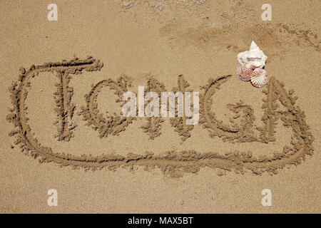Word 'Tonga' written in a sand - travel concept - Stock Photo