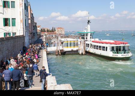Long queue of tourists waiting to board the vaporetto waterbus to Burano Island, Venice,  Veneto, Italy  filling  Fondamenta Nove, Cannaregio in a lon - Stock Photo