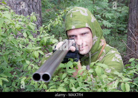 The shooter in camouflage with an old gun - Stock Photo