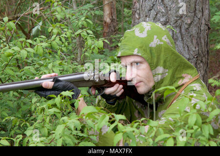 The shooter in camouflage with an old trigger gun - Stock Photo