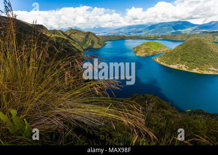 Cuicocha, beautiful blue lagoon in the interior of the Cotacachi volcano crater with spikes of grass in the foreground - Stock Photo