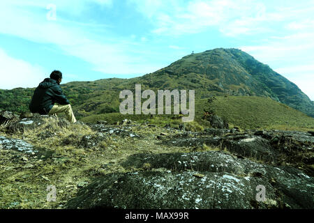 Moment of loneliness. Man sit on the peak of rock and watching into colorful mist and fog in forest valley. - Stock Photo
