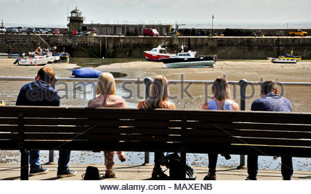 Watching the world go by. Five people sitting on a bench overlooking the harbour at St Ives, Cornwall, England, UK - Stock Photo